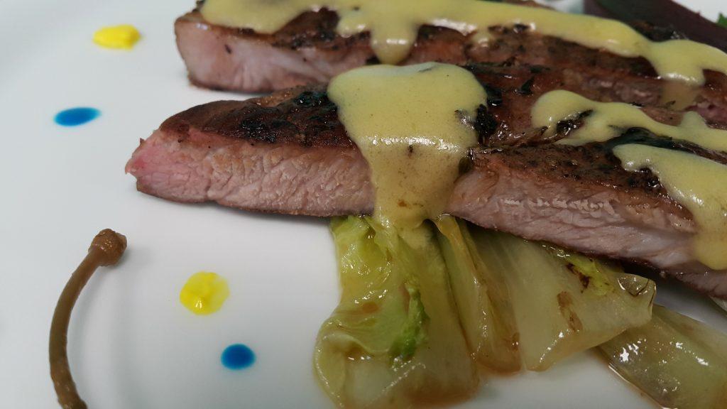 свинска вратна пържола су вид, довършена на тиган и сервирана с червено цвекло на су вид, сотирана маруля, сос и каперси.